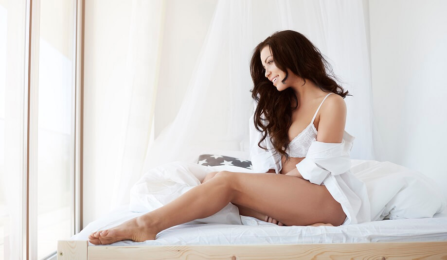 sexually aroused women sitting on bed
